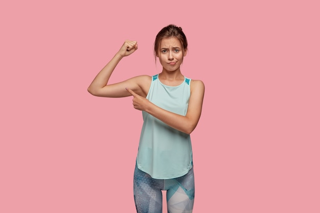 Zdjęcie wysportowanej kobiety ma niezadowolony wyraz twarzy, podnosi rękę, by pokazać mięśnie, wskazuje na biceps, nosi casualową koszulkę i legginsy, odizolowane na różowej ścianie. koncepcja szkolenia