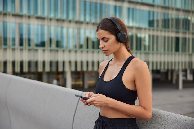 Zdjęcie wysportowanej modelki wybiera piosenkę na trening pobiera piosenkę do swojej playlisty biegowej ma przerwę po treningu nosi sportowe pozy w nowoczesnym otoczeniu