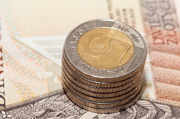 Zdjęcie z bliska, na którym na papierowym pieniądzu leży polska moneta. złoty, mała głębia ostrości