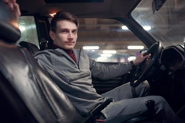 Zdjęcie z boku mężczyzny patrzącego na kamerę siedzącego w samochodzie