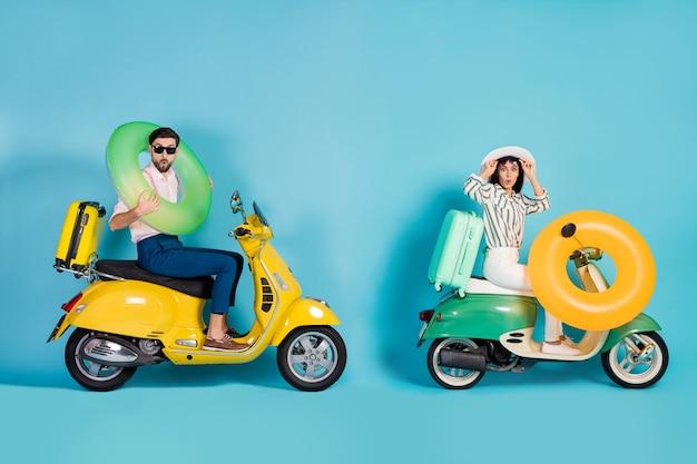 Zdjęcie z boku profilu całego ciała zaskoczonych dwóch osób jeźdźców kierowcy podróżują latem wakacje wybrzeże morskie motocykl nosić pierścień gumowe bojki ratunkowe bagaż pod wrażeniem izolowana niebieska ściana