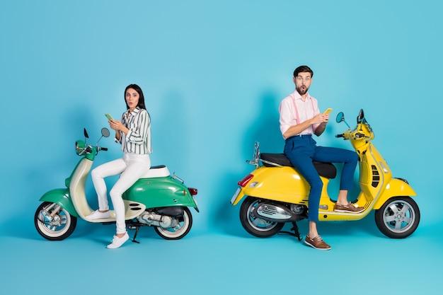 Zdjęcie z boku profilu całego ciała zdziwiony dwie osoby żona mąż jeździec siedzieć chopper używać telefonu komórkowego pod wrażeniem nawigacji gps myślę, że zgubiona odzież formalna izolowana niebieska ściana
