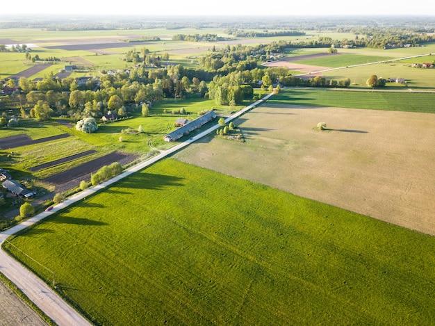 Zdjęcie z drona zielonego łąki obok pola rolnego z polną drogą i wioską wiejską