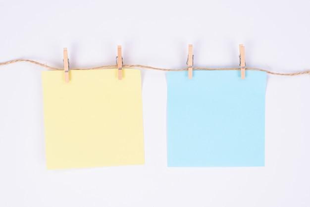 Zdjęcie z dwóch kwadratowych arkuszy papieru wiszące na liny na białym tle biały kolor