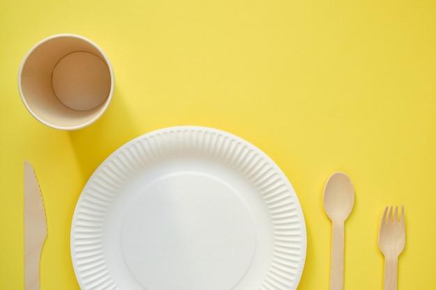 Zdjęcie z góry białego kartonowego talerza z drewnianą łyżką po prawej stronie i brązowym kartonowym szkiełkiem po lewej na żółtym tle
