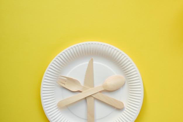 Zdjęcie z góry białego kartonowego talerza z nożem, łyżką i drewnianym widelcem w środku na żółtym tle