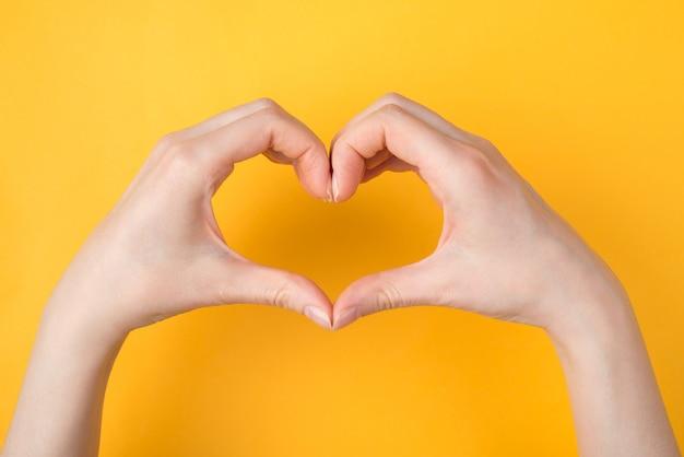 Zdjęcie z góry nad głową przedstawiające kobiece dłonie, które sprawiają, że serce jest izolowane na jasnym, żywym tle w kolorze żółtym