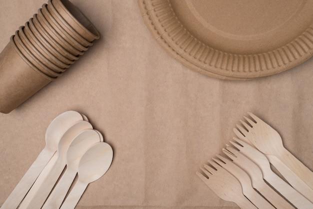 Zdjęcie z góry nad widokiem z góry na drewniane sztućce, papierowe kubki i talerze umieszczone w rogach, dzięki czemu centrum jest puste na białym tle na stole z papieru rzemieślniczego