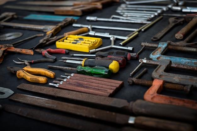 Zdjęcie z góry ogromnej kolekcji roboczej i ręcznej elektronarzędzi wielu do drewna na odosobnionej czarnej powierzchni
