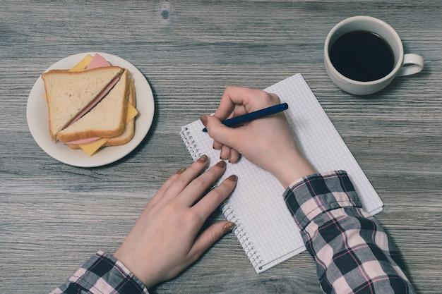 Zdjęcie z góry pierwszej osoby przedstawiające ręce kobiety trzymającej pióro nad płytką notatnika