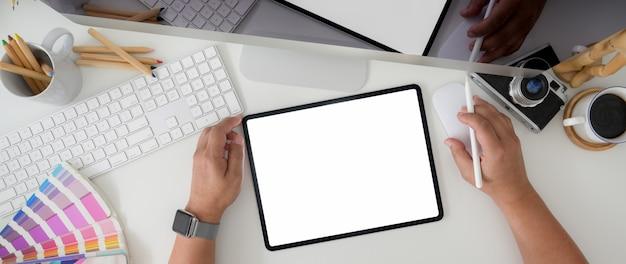 Zdjęcie z góry projektanta pracującego na tablecie z aparatem komputerowym i materiałami eksploatacyjnymi projektanta