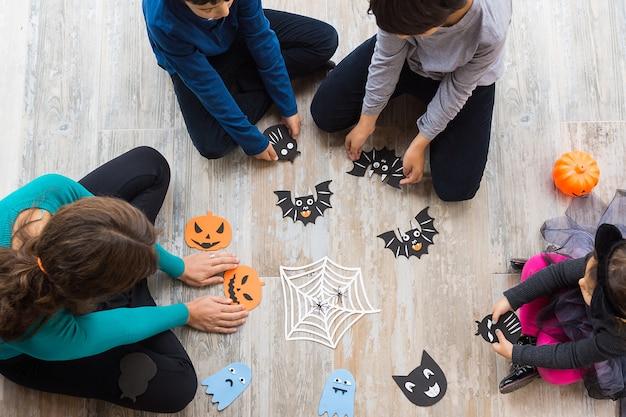 Zdjęcie z góry przedstawiające dwóch chłopców i dziewczynkę z matką siedzących na podłodze, wykonujących rękodzieło do dekoracji na halloween