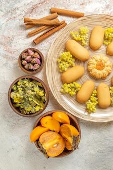 Zdjęcie z góry przedstawiające talerz ciastek i lasek cynamonu oraz suszone kwiaty i palmy