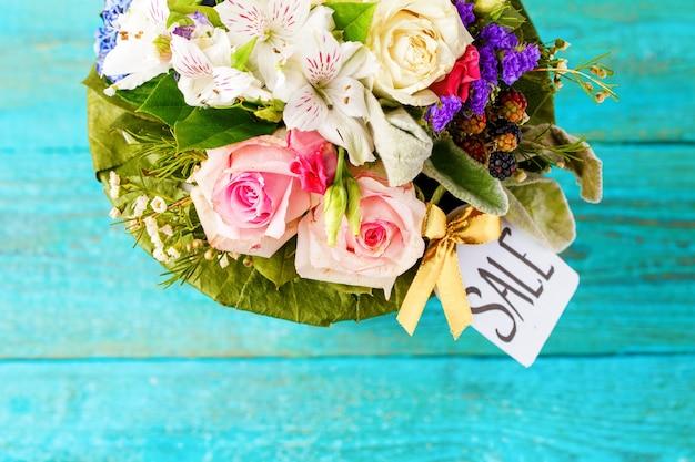 Zdjęcie z góry romantycznego bukietu różowych róż, lilii, zielonych liści na drewnianym niebieskim tle