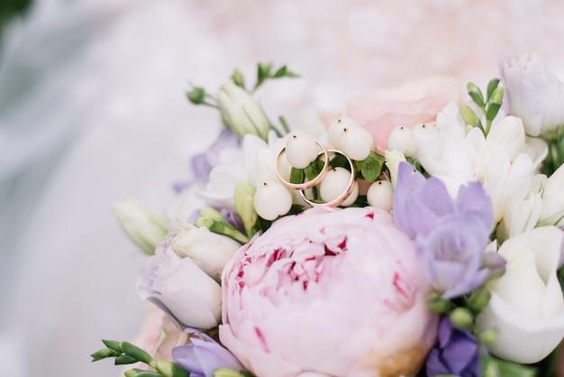 Zdjęcie z obrączkami leży na bukiecie kwiatów