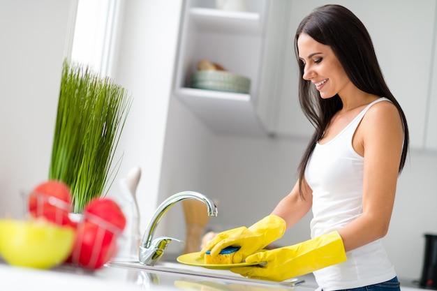 Zdjęcie z profilu przedstawiające zgrabną, pozytywną gospodynię myjącą naczynia po kolacji w żółtych gumowych rękawiczkach ochronnych trzymaj gąbkę czuć komfort w kuchni w pomieszczeniu