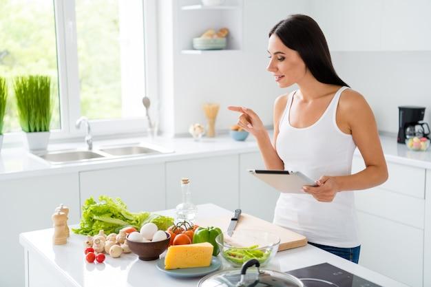 Zdjęcie z profilu uroczej, słodkiej, brązowowłosej gospodyni domowej, która chce gotować poranne śniadanie podążaj za przepisem policz składniki warzywa ser grzyby czerwony pomidor użyj tabletki w kuchni w białym domu