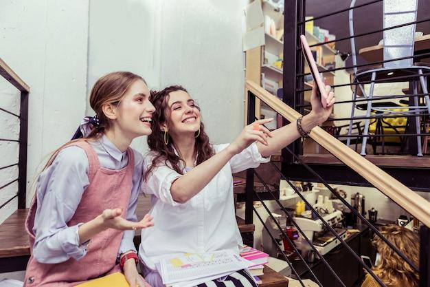 Zdjęcie z przyjacielem. pozytywne panie z białymi mocnymi zębami robiące selfie siedząc na schodach w stołówce
