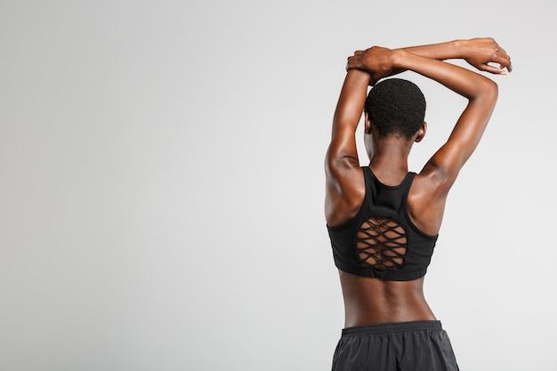 Zdjęcie z tyłu afroamerykańskiej kobiety rozciągającej ramiona podczas ćwiczeń na białym tle nad białą ścianą