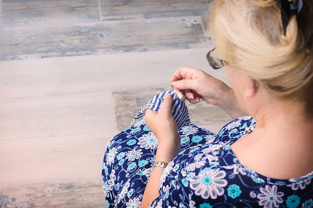 Zdjęcie z tyłu blond kobiety w niebieskiej sukience z drukowanymi kwiatami
