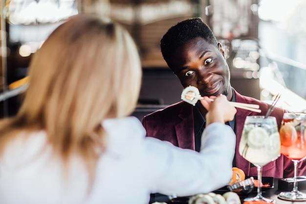 Zdjęcie z tyłu, blondynka karmiąca swojego chłopca sushi rolki na letnim tarasie. szczere emocje.
