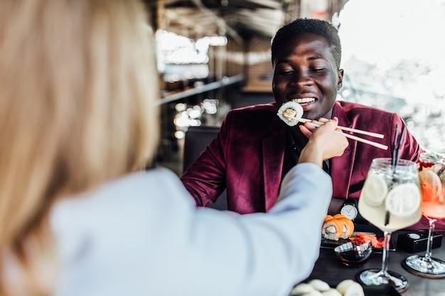 Zdjęcie z tyłu, blondynka karmiąca swojego chłopca sushi rolki na letnim tarasie.
