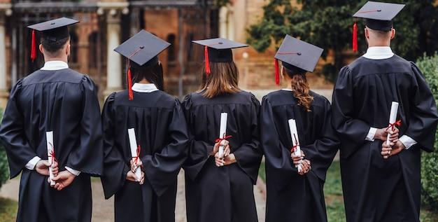 Zdjęcie z tyłu grupa studentów posiadających dyplom