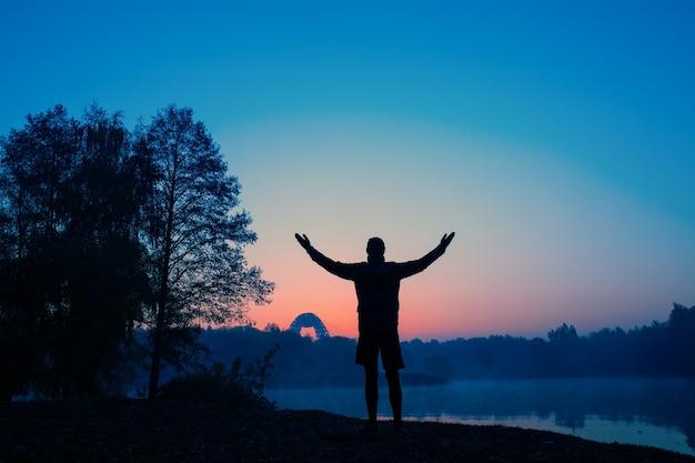 Zdjęcie z tyłu mężczyzny z rękami w górze o zachodzie słońca