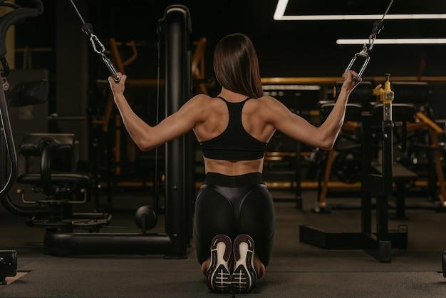 Zdjęcie z tyłu wysportowanej kobiety, która na kolanach wykonuje pionowe pchnięcie w skrzyżowaniu obu bloków maszyny kablowej. umięśniona dziewczyna nosi na siłowni top i elastyczne szorty z wysokim stanem.