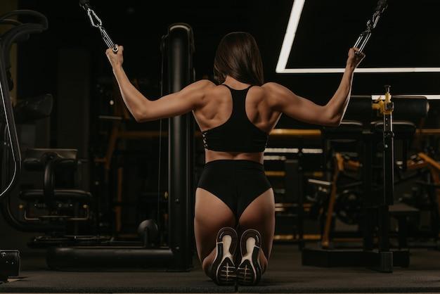 Zdjęcie z tyłu wysportowanej kobiety, która na kolanach wykonuje pionowe pchnięcie w skrzyżowaniu obu bloków maszyny kablowej. umięśniona dziewczyna nosi top i krótkie spodenki z wysokim stanem na siłowni.