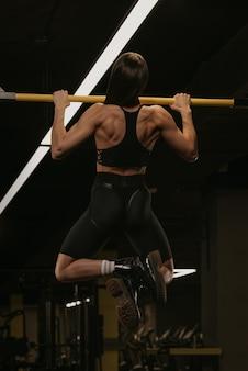 Zdjęcie z tyłu wysportowanej kobiety, która na siłowni wykonuje podciąganie z szerokim uchwytem. umięśniona brunetka nosi czarny top i elastyczne szorty z wysokim stanem podczas treningu pleców.