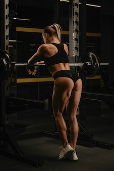 Zdjęcie z tyłu wysportowanej kobiety o blond włosach leżącej na sztangie na stojaku do przysiadów na siłowni