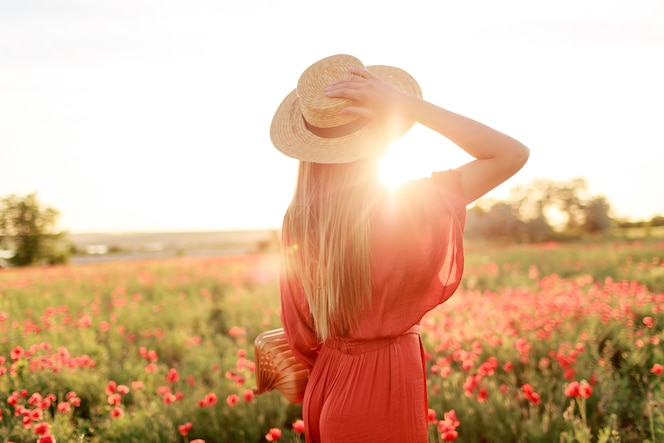 Zdjęcie z tyłu zainspirowanej młodej kobiety trzymającej słomkowy kapelusz i patrzącej w horyzont. pojęcie wolności. ciepłe kolory zachodu słońca. pole maków.
