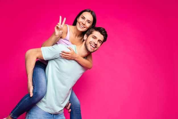 Zdjęcie zabawnego beztroskiego faceta i pani trzymających piggyback pokazujące symbol v-znak noszą ubranie na białym tle w żywym różowym kolorze