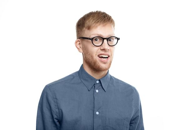 Zdjęcie zabawnego, emocjonalnego, młodego nieogolonego mężczyzny w stylowych okularach, otwierającego usta ze zdumienia, zszokowanego niespodziewanymi wiadomościami, wpatrującego się w pełne niedowierzanie. szok i zaskoczenie