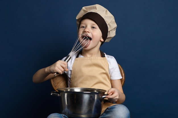 Zdjęcie zabawnego europejskiego małego chłopca w fartuchu i czapce szefa kuchni, trzymającego rondel i liżącego trzepaczkę w dłoniach, degustującego sos podczas samodzielnego gotowania makaronu, z radosnym wyrazem twarzy