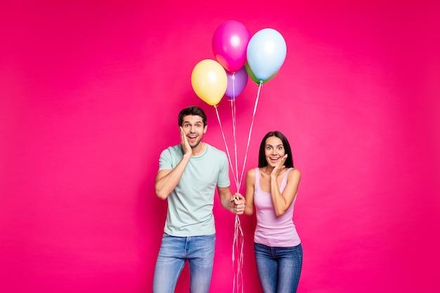 Zdjęcie zabawnego faceta i pani trzymających balony z powietrzem na policzkach nie wierzą w nieoczekiwaną niespodziankę ze strony przyjaciół, noszą swobodny strój na białym tle różowy kolor tła