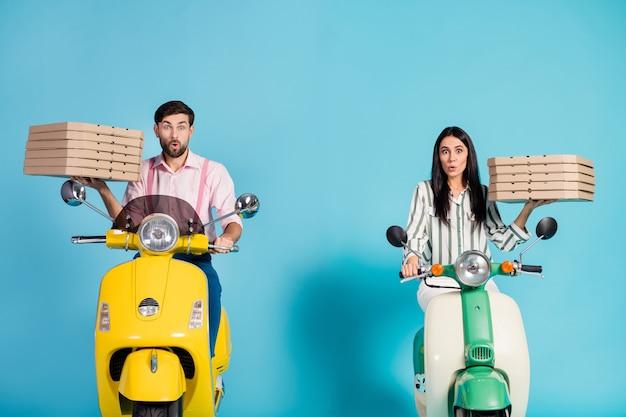 Zdjęcie zabawnej pani facet z otwartymi ustami jeżdżą dwoma motorowerami vintage nosić papierowe pudełka po pizzy zawód kuriera szybka dostawa fastfoodów fastfood odzież formalna strój izolowany niebieski kolor ściana