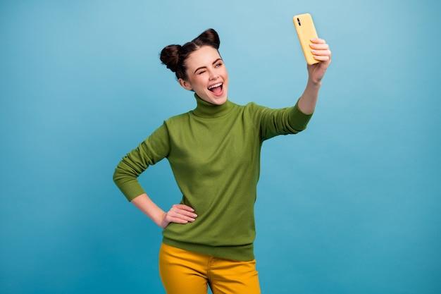 Zdjęcie zabawnej, zalotnej pani trzymającej telefon za rękę, robiąc selfie, strzelając do bloga mrugające okiem zwolennicy noszą zielony golf żółte spodnie na białym tle niebieski kolor ściana