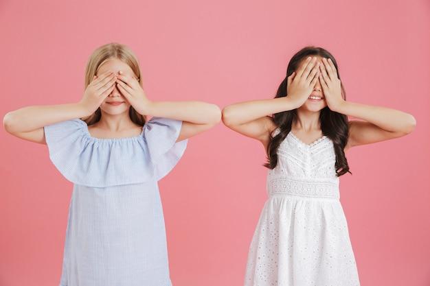 Zdjęcie zabawnych małych dziewczynek w wieku 8-10 lat ubranych w sukienki i zakrywające oczy rękami, na białym tle na różowym tle