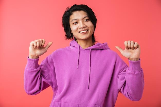 Zdjęcie zachwyconego azjatyckiego faceta w bluzie, radującego się i wskazującego palcami na siebie na białym tle nad czerwoną ścianą