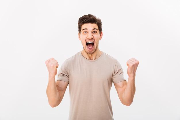 Zdjęcie zachwyconej brunetki krzyczącej i zaciskającej pięści jak zwycięzca lub szczęściarz, na białym tle nad białą ścianą