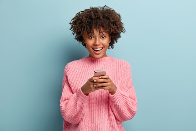 Zdjęcie zachwyconej pięknej kobiety trzymającej telefon komórkowy, pisze sms-y, podłączona do bezprzewodowego internetu, surfuje na czacie online, nosi duży sweter, stoi w domu, wybiera zdjęcie na swoją stronę internetową