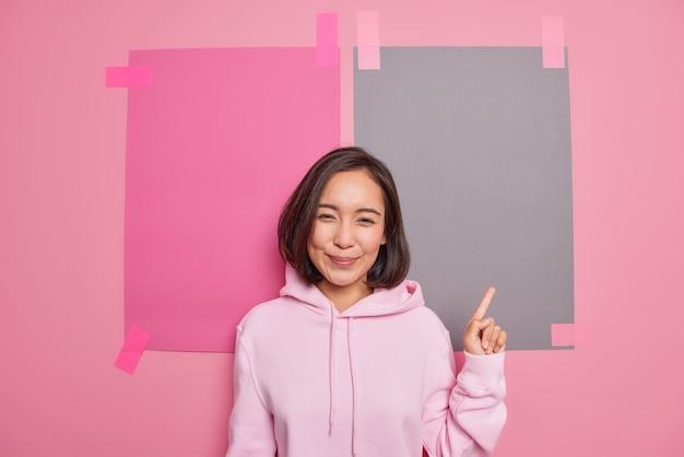 Zdjęcie zachwyconej zadowolonej kobiety o wschodnim wyglądzie skierowanym w górę daje informację pokazującą pustą przestrzeń