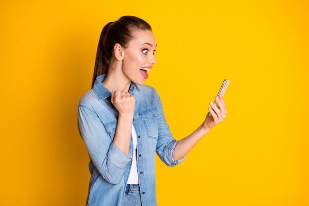 Zdjęcie zachwyconej zdziwionej podekscytowanej dziewczyny używa telefonu komórkowego pod wrażeniem zwolenników mediów społecznościowych subskrybenci podnoszą pięści nosić styl stylowe modne ubrania na białym tle jasny połysk kolor tła