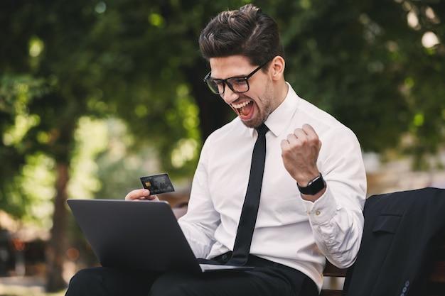 Zdjęcie zachwycony biznesmen w garniturze siedzi na ławce w zielonym parku i pracuje na laptopie w słoneczny dzień
