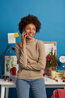 Zdjęcie zadowolonego afro american freelancera stoi we własnej szafce w domu, prowadzi rozmowę telefoniczną, patrzy na bok z szerokim uśmiechem, pozuje przy biurku z lampką biurkową