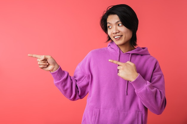 Zdjęcie zadowolonego azjatyckiego faceta w bluzie, radującego się i wskazującego palcami na copyspace na białym tle nad czerwoną ścianą