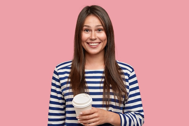 Zdjęcie zadowolonej brunetki ubranej w swobodny sweter w paski, pije kawę na wynos