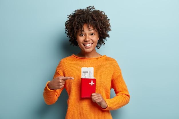 Zdjęcie zadowolonej ciemnoskórej, kręconej kobiety podróżującej wskazuje na bilety i paszport, cieszy się z wyjazdu za granicę na letnie wakacje